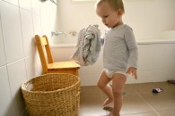 a-little-boy-puts-clothes-to-the-laundry-basket