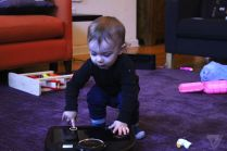 Toddler plays robot vacuum