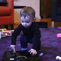 Toddler plays robot vacuum