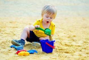 Toddler plays sand